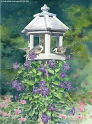 White birdhouse in garden with clematis and hummingbird